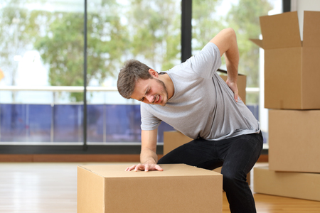 man suffering back ache moving boxes in his new house